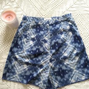 Lyseblå shorts med blåt og hvidt mønster. Sidder til i taljen. Har lommer.