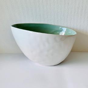 Elegant og smuk skål fra OpenMind. En smuk detalje til hjemmet med dens spændende geometriske form. Udført med hvid glasur udenpå og jadegrøn glasur indvendig. Højde: 17,5 cm Længde: 31 cm Bredde: 23 cm