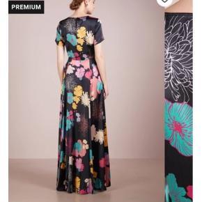 Helt nyt.   Luksuriøs maxikjole fra Stine Goya i blød, kvalitetssilke. Nanna Dress har sort bundfarve med et skønt univers af multifarvede blomster. Stine Goya Nanna Dress, Flowers Dark har knaplukning i nakken, korte ærmer, fastsyet stykke i taljen og masser af vidde forneden. Kjolen er lavet i lækker silke-kvalitet mixet med elastik for en udsøgt pasform.