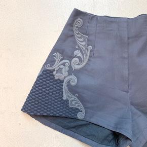 Mørk grålig farve med lidt blå undertoner. No brand. Måler 67 cm i taljen, omkring 108 over numsen og omkring 37 cm i længden (de er kortere i siden)