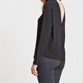 Sort bluse i tyndt stof fra Envii med dyb udskæring i ryggen og tre knapper i halsen.   En smule gennemsigtigt, men ikke meget. Løs i størrelsen.