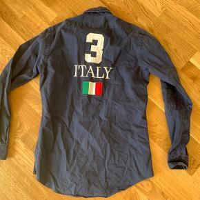 Navyblå skjorte m. tryk af mærket Ralph Lauren i str. S. Fremstår i rigtig god stand. Fragt er som udgangspunkt ikke inkluderet i prisen.  Jeg har lige nu et stort udvalg af tøj til salg. Hvis du er interesseret i at købe flere ting fra mig, så er jeg åben for at lave en god deal.