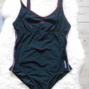 Flot Ny badedragt i sort og rød. Er uden brystskål. Længde 77 cm Brystvidde: 78 cm  Sendes med DAO. Inkl porto.