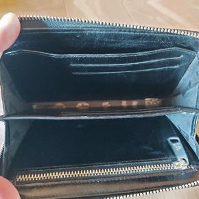 Skøn clutch/pung i sort med guld... Man kan se på lynlås ...se billede...er brugt...derfor sat under gmb Sælges for prisen på annoncen plus porto