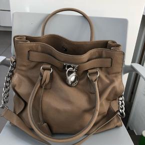 Skuldertaske i farven mørk  beige/ lys brun med enkelte brugsspor på læderet/ pletter. Mål 33 *37•12 cm. Nypris 2800 kr.