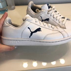 Hvid sko med mørkeblå Puma.  Slid ses på billederne