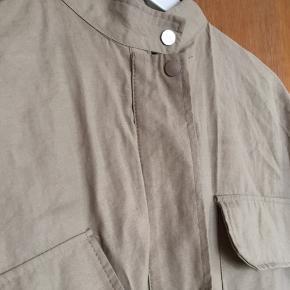 Helt ny og rigtig lækker playsuit (buksedragt med shorts) fra Storets i safaristil og med fine detaljer. Lækkert materiale og sidder godt. Perfekt til sommeren.  Den er aldrig brugt og har stadig prismærket i.