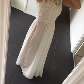 Smuk brudekjole, brugt en gang, er købt ved søstrene Skårup i Snedsted. Todelt kjole, selve kjolen er der en smule rosa i. Der er nogle enkelte pletter på den, en enkelt foran på blonden, er ikke blevet renset. Nypris over 4000kr.