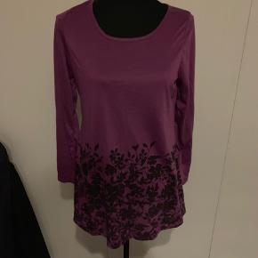 Lilla bluse med sorte blomster str xl men svarer til  m/L.   Aldrig brugt.  Køber betaler Porto.