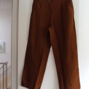 Varetype: Bukser / Nye Størrelse: 44 Farve: Gylden/ brun Oprindelig købspris: 499 kr.  Flotte, spritnye bukser med vide ben . Viscoseblanding i en let skinnende kvalitet Har lommer-  Taljevidde ca. 85 cm Indvendig benlængde ca. 81 cm