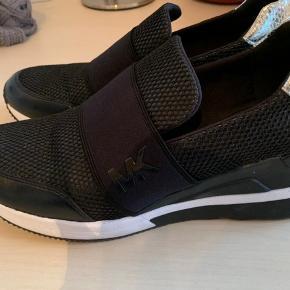 Lækker sneakers fra Michael Kors med lidt forhøjet hæl i selve skoen. Behagelig og smart, men jeg kan desværre ikke gå i den.