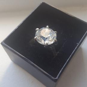 Jeg købte ringen for lang tid siden, men den var i en forkert størrelse. Det var for dyrt at returnere den, så har beholdt den indtil nu. Nu vil jeg egenlig gerne sælge den, da jeg har aldrig brugt den.  Den er lavet i tin og der er ingen mærker på den. Størrelsen er N, hvilket svare til 16,92 mm i diameter. Mærket er Alchemy England.