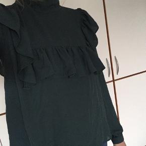 Fin mørkegrøn bluse med flæser/peplum. Den er lidt mere farvemættet end man kan fange på billeder.  Lille kig til ryggen. Kan hentes på Nørrebro eller Indre by eller sendes med DAO :)