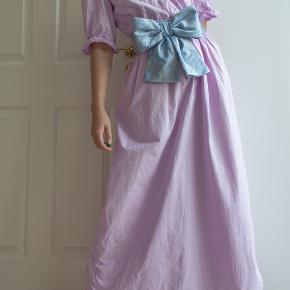 A delicate purple dress from vintage shop in Italy. The belt is set on the back, but can be easily removed if you want.  Looks great with a wide belt on too.  Size 38/40, waist up to 92cm, opens with buttons on the front. No marks inside. Just washed.  You are welcome to visit my vintage website redvintage.dk for more pictures. New collection on the website every week.