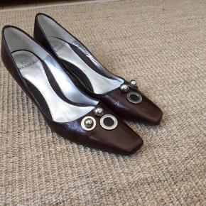 """Skoene har kun været brugt en enkelt gang.  Bemærk den flotte detalje med hælen i """"metal"""" Desværre er der en lille farve forskel på metal ringen på den venstre sko. Prisen er sat derefter. Skoene er i ægte skind med lædersål."""