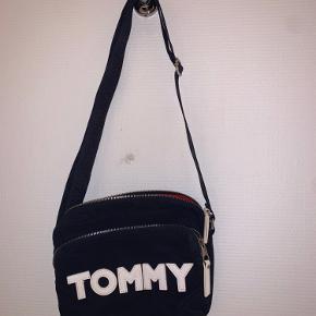 Tommy Hilfiger taske der er rød inden i. Har god plads til mange ting. Brugt 1-2 gang højst. Rigtig fin kvalitet og flotte farver. Byd!