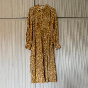 Blomstret karrygul kjole fra H&M. Pæn stand - uden pletter, huller o.lign. Str. 36.