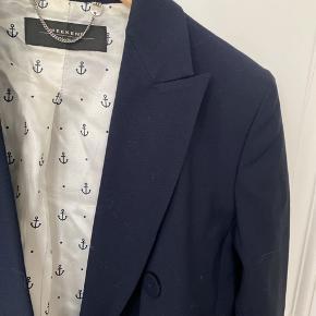 Super lækkert blazer fra Max Mara Weekend i uld/viscose/elestane blend dobbel knappet med stofbetrukket knapper midt for samt 3 mindre ved ærne. Super fin klassisk pasform