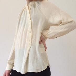 Fineste silkeagtige skjorte med meget flot asymmetrisk knapning foran. Lille plet ved sømmen som måske kan komme af men jeg er ikke sikker, derfor sælges den billigt!