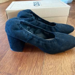 Flotte sorte sko i imiteret ruskind. Skoene har ikke været brugt og fremstår som nye med original æske. Sidder behageligt på foden pga elastik i kanten. Kan afhentes på Christianshavn.