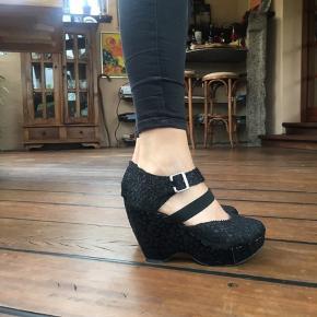 Sorte plateau sko med mange detaljer.