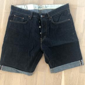 Klassiske mørke jeans uden slid, med opbuk som kan tages ned.  Kvalitet: 100% Bomuld Farve: Ensfarvet mørkeblå  Livvidde: 94cm. Benlængde: 22cm. (Innersømmen med opbuk