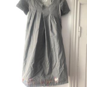 Smuk og speciel kjole fra en af de allerførste kollektioner. Kjolen er i tykt denim-agtigt stof. Den sidder til over skulder og bryst. Kjolen har fin håndbrodering nederst og et bælte der kan spændes for eller bag. Det er en 38, men vil passe en 36 eller lille 38. Bytter gerne hvis nogen tilfældigvis har den i 40. Pris 375 pp