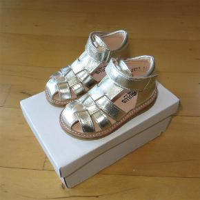 """Varetype: Sandaler *NYE* Farve: Champagne  Lækre sandaler fra Angulus, som aldrig har været brugt.  De måler ca. 13,3 cm indvendigt.  Farven er """"Champagne"""".  Bud fra 390 kr. pp.  Medmindre andet aftales, sender jeg med DAO til DK adresser.  Jeg bytter ikke, men handler gerne via Mobilepay :-)"""