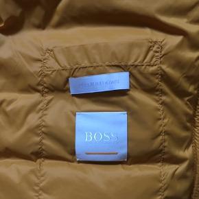 Lækker varm dunjakke (efterår/vinter) i mærket Boss. Med dejlig hætte og lommer i siden - snor forneden, så den kan strammes til. Den har aldrig været brugt, da den er købt et nummer for stor. Farven er smuk gylden(okkerfarvet/gul). Nypris 1800kr - sælges for 800 kr, og prisen er fast. Mener den kan passe str. 42 og 44.  En meget anvendelig klassisk jakke. Bytter ikke