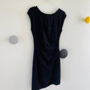 Den 'klassiske' sorte kjole med smuk rynkeeffekt i siden, så den sidder super godt på alle kropsformer og giver en smuk figur