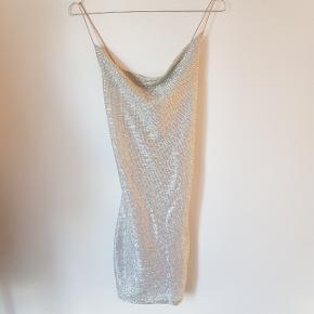 Ubrugt sølv kjole med krysende stropper på ryggen. Lårkort og med cremefarvet underkjole.   Den skinner som på første billede. Lidt svært at se på billede to