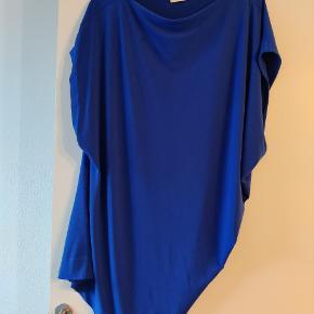 Flot blå farve. Asymmetrisk bluse der giver rynke effekt ved hoften når den er på.