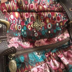 Stor, rummelig Oilily taske, med 3 mindre inderlommer + 3 yderlommer med lynlås. Tasken lukkes med lynlås øverst og har udover 2 mindre hanke en stor skulderrem som kan klipses af og på. Tasken er generelt i rigtig god stand, men med slidtage på hankene og på hjørnerne under tasken (se sidste billeder).