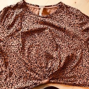 Kort crop top t-shirt leopard mønstret. Bomuld. Fastsyet knude. Brugt få gange.   33,- + fragt, sender med Dao kr. 37,- Kan afhentes i Odense.  Bytter ikke.  Mængderabat 💗