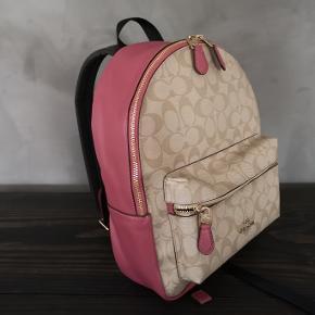 Lækker rygsæk i rosa læder fra Coach med beige logo print. Jeg har aldrig brugt den så den er helt ny.   Højde ca 35 cm og bredde ca 30 cm