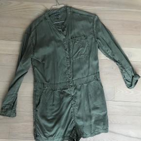Tommy Hilfiger buksedragt med korte ben. Købt i sommers, brugt to gange.  Har stropper til bælte og knappelukning foran.  Den er grøn/army i farven Modellen hedder THDW jumpsuit short 52 Nypris var 1100 kr.