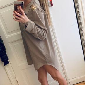 Beige skjorte kjole med guld knappet og guld  palietter på skulderen. Jeg er en str XS, så hvis du er str L, vil det nok være mere en skjorte end en kjole :)