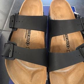 Helt nye sandaler fra Birkenstock i sort.  BIRKENSTOCK Arizona er en ægte klassiker. Denne individuelt indstillelige med to remme, unik og unisex. De er meget behagelige at gå i.  Det er en bred model.  Måler 28,5 cm (din fødder er mindst 28 cm) og der skal kun være pr mm mellem hælene/tæerne. Mange køber for store.  Nypris 750,-  MP 450,- pp