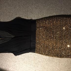 """Virkelig flot og elegant kjole som sidder virkelig flot.  Prøvet på, men aldrig brugt. Sort overdel med """"gennemsigtig"""" ryg og underdelen er fyldt med guldpalietter. Lynlås i ryggen. Str. 10, svarende til str. S. Nypris: ca. 350 kr. Pris: 180 kr.  Åben for bud ved hurtig handel"""