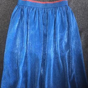 Fineste nederdel i metallic look med elastik i taljen.