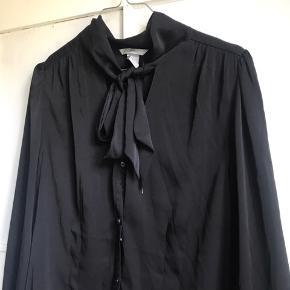 Sort silke-agtig skjorte med bindebånd i halsen og knapper foran.   Jeg sender gerne - køber betaler fragt 📦 Bytter ikke.