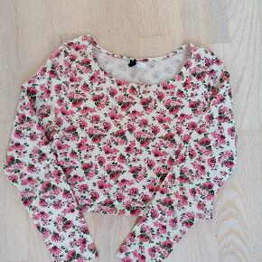 Langærmet crop-top fra H&M i str. M/ca. 38. Hvid baggrund med rosen-motiv i lyserød/rosa og grønne blade. 95% bomuld, 5% elastan  Købt brugt, men kun iført et par gange, ellers i god stand.