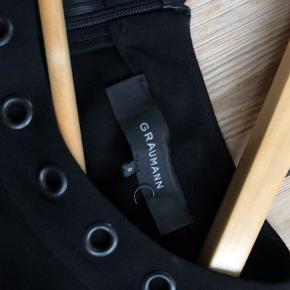 """Utrolig fin, sort, klassisk kjole med indsnit ved bryst og talje.  Trekvart lange ærmer med """"nitter"""" ved krave og ærmekant - en smule tætsiddende omkring armene.  Kjolen har en lynlås i ryggen.  Mål.  Længde: 91cm. fra krave til kant Bredde (skuldre): 36 cm.  Kjolen er lavet af 100% viscose."""