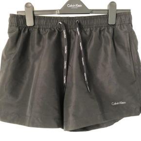 Calvin Klein Swimwear * Helt nye og ubrugt stadig med prisskilt på.  * Nypris 449 kr * Materiale: 100% polyester * For: 100% polyester * Plejeanvisning: Maskinvask ved 30°C  * Med baglommer og sidelommer