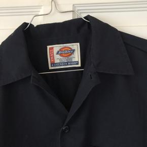 Fin mørkeblå, kortærmet skjorte fra Dickies. Str S, tænker den er unisex. Jeg er en str 38 (S/M), og jeg passer den fint.  Sendes med DAO. 😊