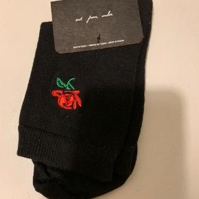 Sorte sokker med rød rose fra UO i str. One size. Materiale bomuldsmix - se billede. (Porto r 10, såfremt brevpost)