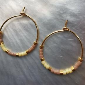 1 par små creoler (20mm) i forgyldt messing med forgyldte Delica Beads, matte beige Delica Beads og matte pastelgule Delica Beads.   Stand: Helt nye. Jeg laver dem selv.   Bemærk: Prisen er fast.  Skal hentes på Nørrebro (Ravnsborggade) / mødes på Nørreport ellers kommer forsendelse med DAO oveni.   #øreringe #creoler #håndlavet #smykker