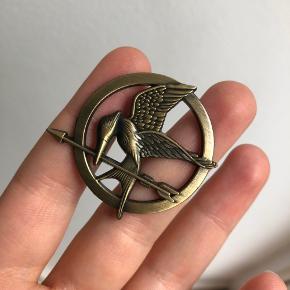 """Jeg sælger denne fine broche / emblem, som er en """"mockingjay pin"""" fra filmen """"the hunger games"""" eller """"dødsspillet"""" på dansk.  Kan sendes mod betaling eller afhentes i Gentofte / Kbh.  BYD :)"""