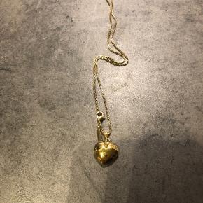 Guld hjerte og lang kæde til bryst.