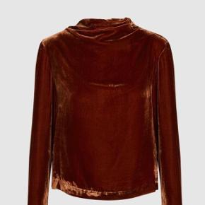 Rustbrun smuk og elegant velourbluse.  Blusen har lange ærmer vide over håndledder og høj hals, der falder i et vandfald med diskret knap til at lukke bagpå foroven.